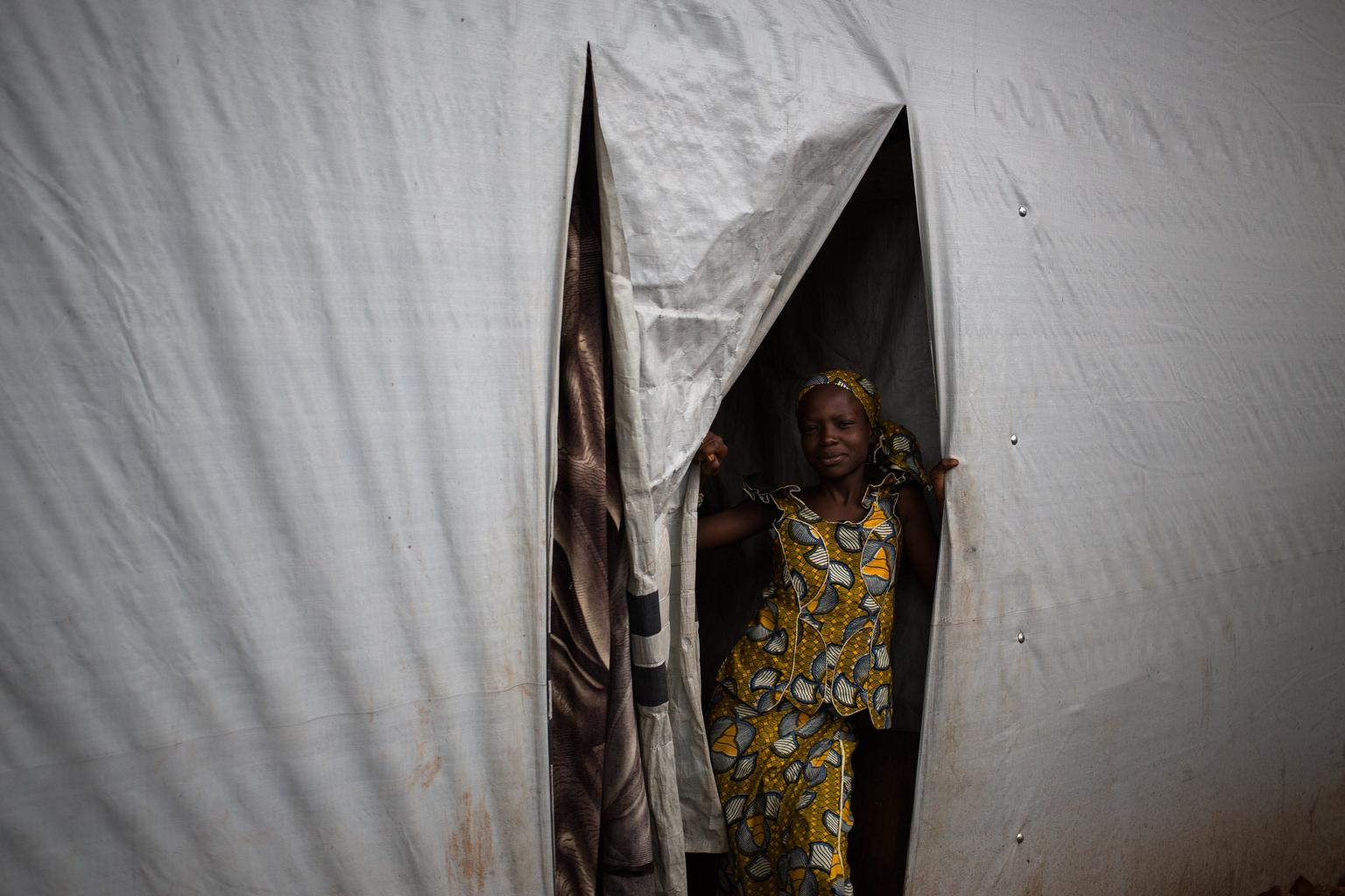 A girl stands at the entrance to the tent where she lives on the grounds of Grand Mosque in Bangui, where displaced Muslim families have taken refuge. July 2014.