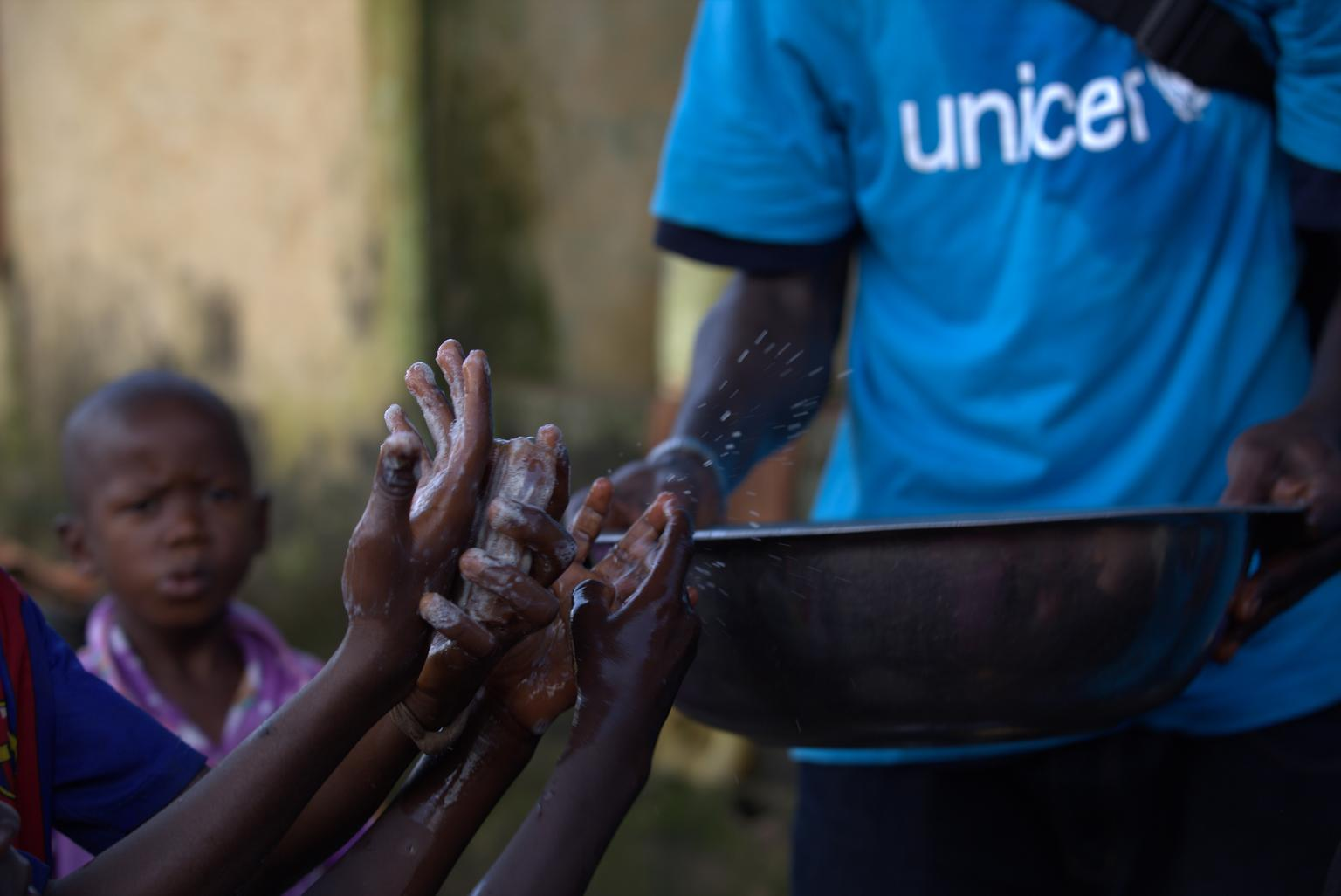 A social mobilizer teaches children about proper hand-washing in Conakry.