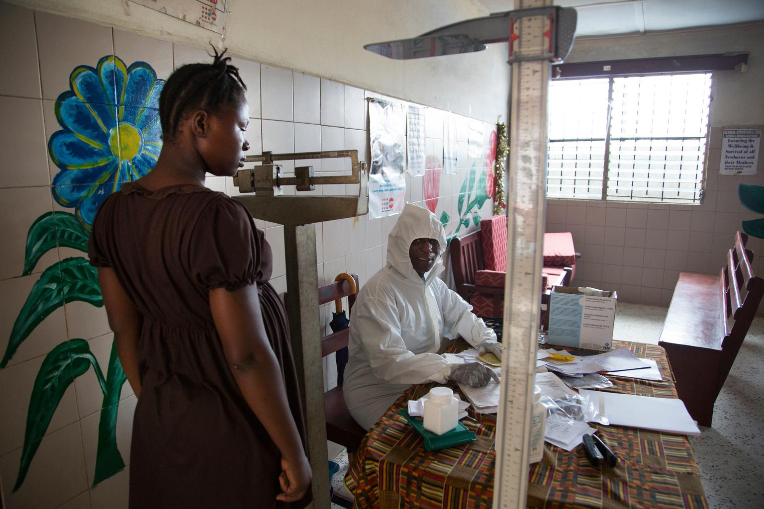 A health worker wearing personal protective equipment conducts a routine antenatal examination of a pregnant woman, at a healthcare facility in Monrovia.