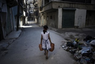 A girl, carries jerrycans of water down a street in Aleppo.