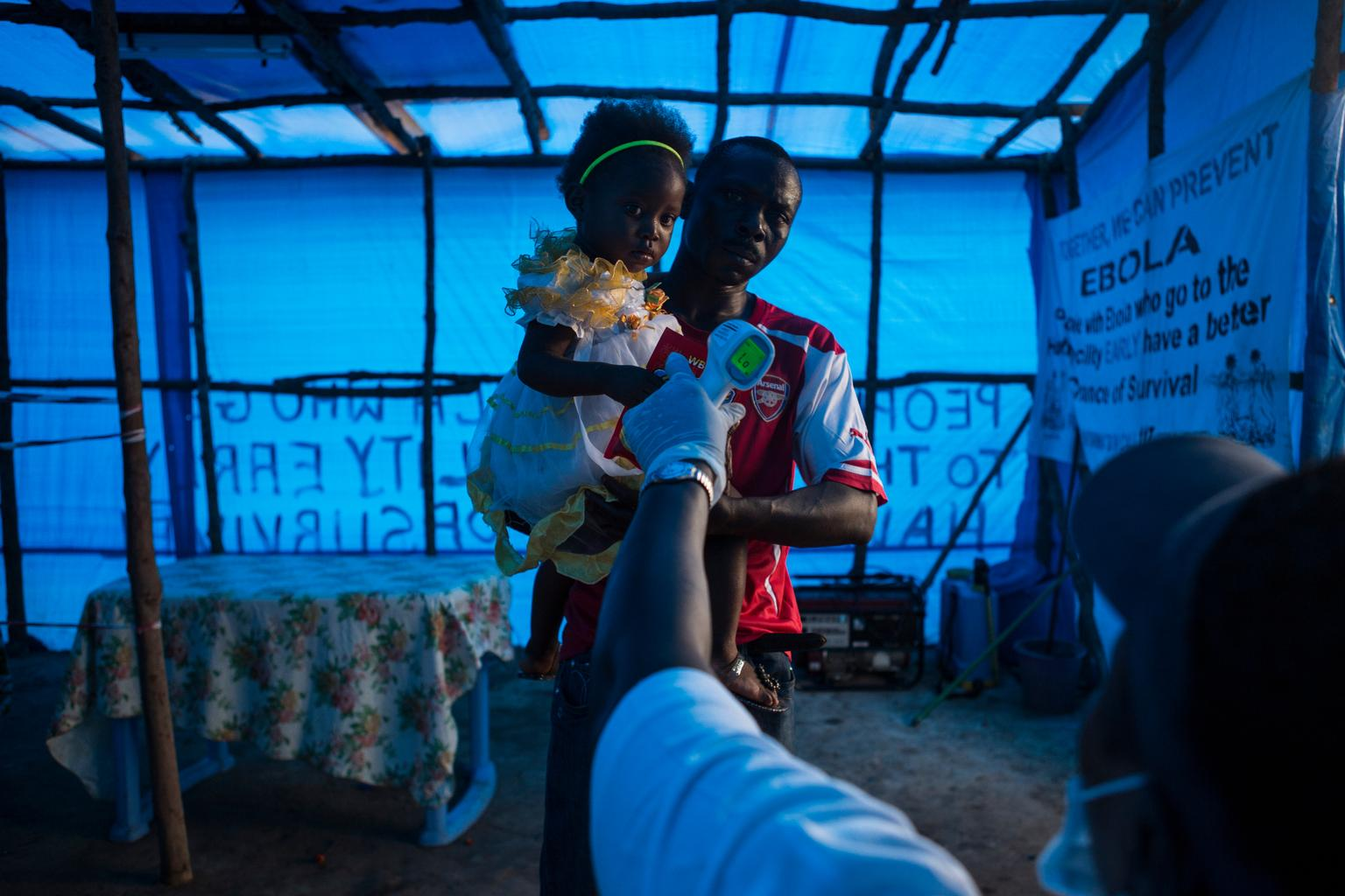 A man and the young girl he is carrying undergo temperature screenings at a checkpoint between the cities of Waterloo and Freetown, Liberia. © UNICEF/NYHQ2014-1813/Bindra