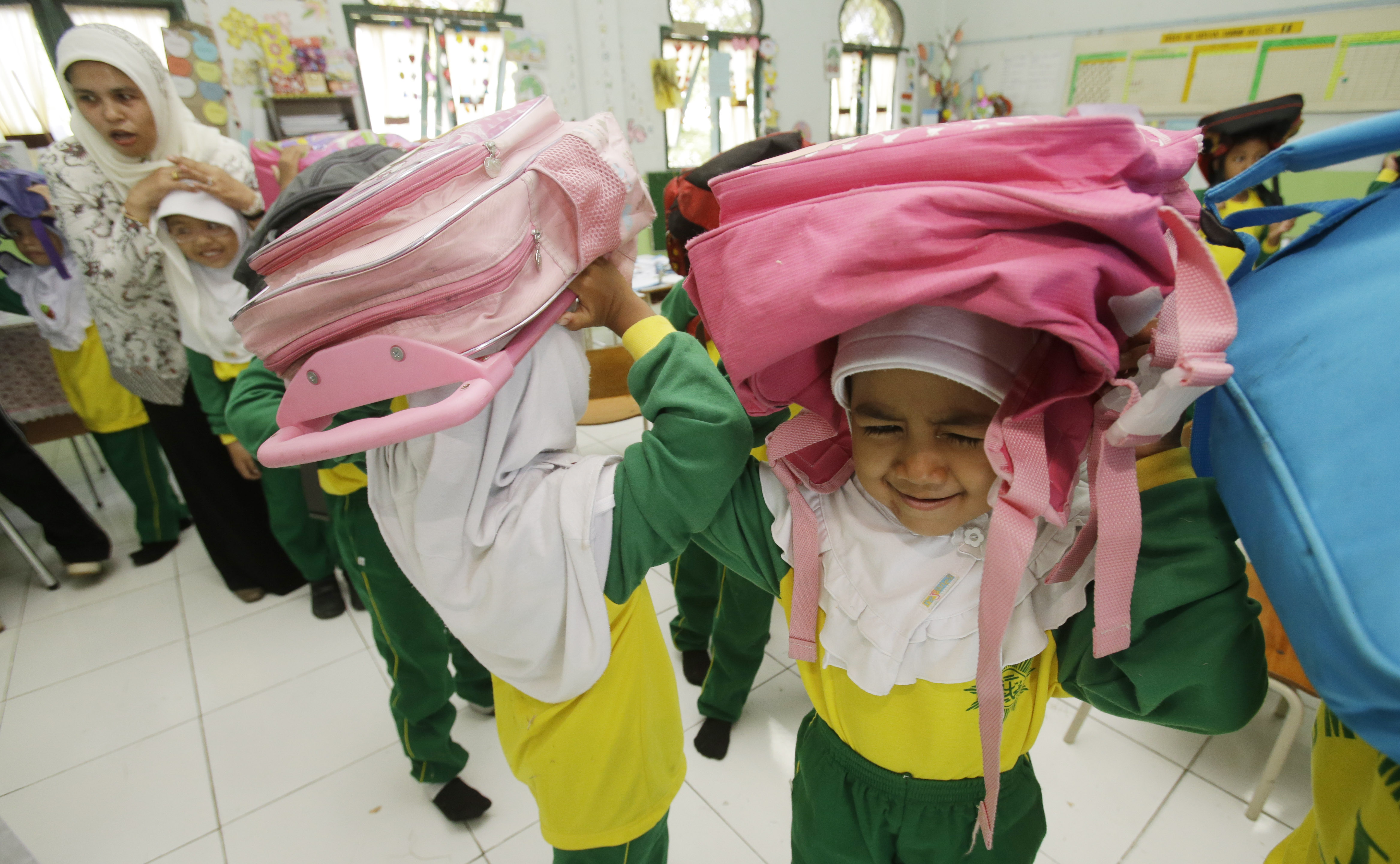 Students protect themselves head with a bag overhead during an earthquake drill at Muhammadiyah 1 Primary school in Banda Aceh. © UNICEF Indonesia/2014/Achmadi