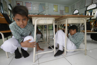 Sheltering under the desks during an earthquake drill at Muhammadiyah Primary School in Banda Aceh. New school buildings were designed to be earthquake-resistant and equipped with desks with thick wooden surfaces bolted to metal legs.