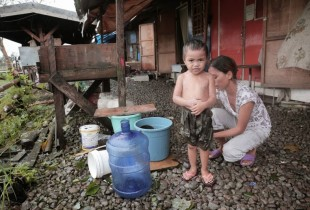 John Dave, 3, has a bath outside a bunkhouse in Tacloban the day after the storm