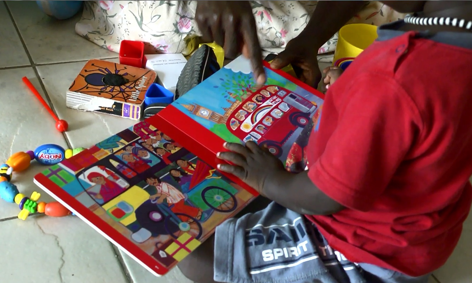 Mawish looks through a book while seated on the floor of the Confident Children out of Conflict Centre.