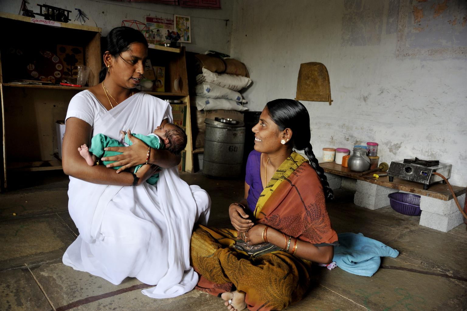 In India, at the Anganwadi Centre, a local Auxillary Nurse Midwife (ANM) trains young mothers who are lactating on the correct technique of breast feeding.