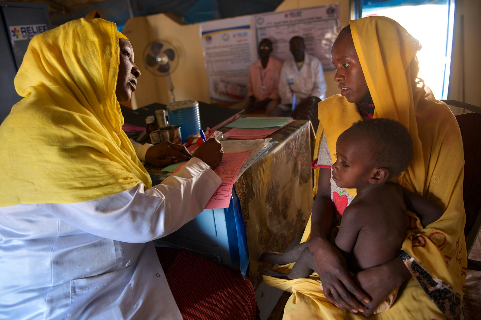 While Bakhita holds her child, a Medical Assistant advises her on how to look after the child's nutrition and growth. A regular nutrition assessment indicated that her child is moderately malnourished.