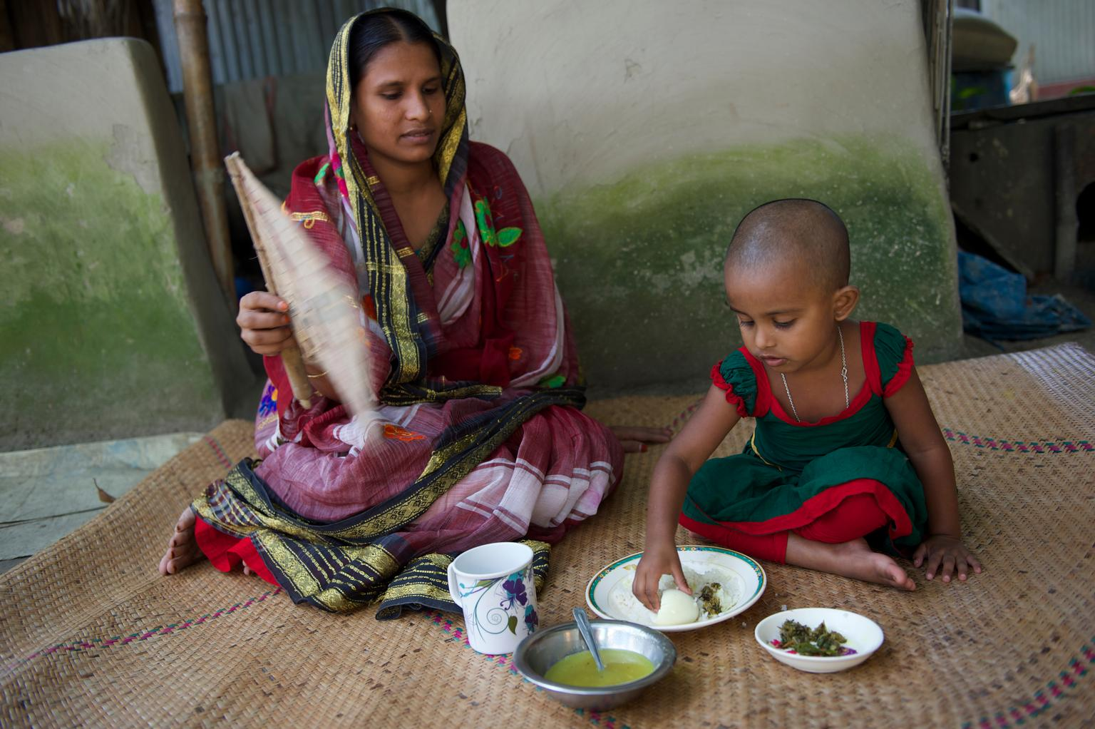 Nishimoni, 3, eats a meal while her mother, Lovely, sits next to her, at home in the village of Char Dhanata, Sharisha Bari Upazila, Jamalpur District, Dhaka Division. When the family began participating in a project that is part of the UNICEF/EU-supported nutrition security programme, Nishimoni was diagnosed with malnutrition. Lovely began receiving packets of micronutrient powder (MNP) from a local clinic; sprinkling the powder on Nishimoni's food helped to improve her nutritional status.  © UNICEF/NYHQ2014-3269/Noorani