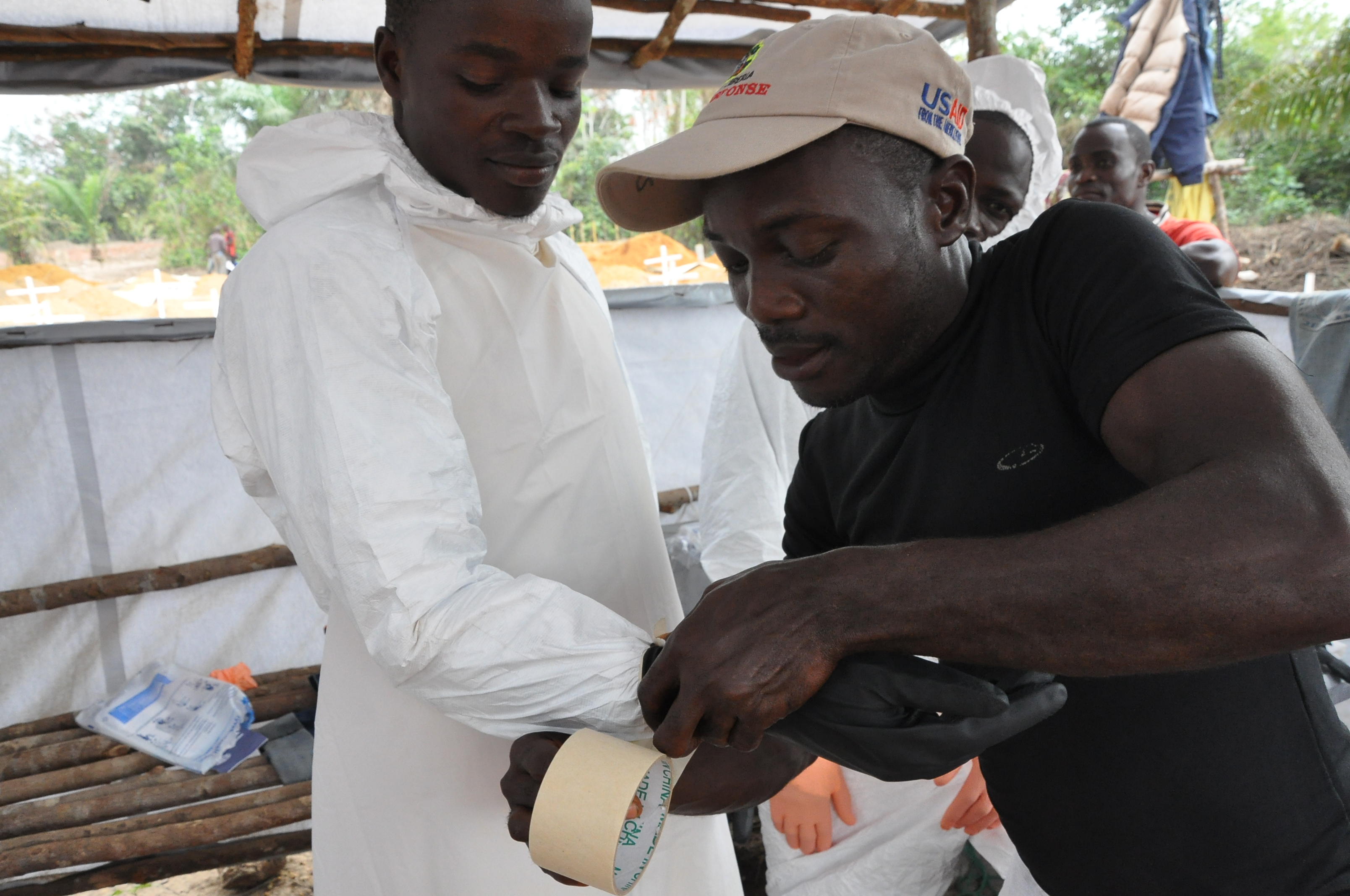 The gloves of the burial team members are taped to the overhaul suits to make sure that there are no gaps where the skin can be exposed. (c)UNICEF/Liberia/2015/Ryeng
