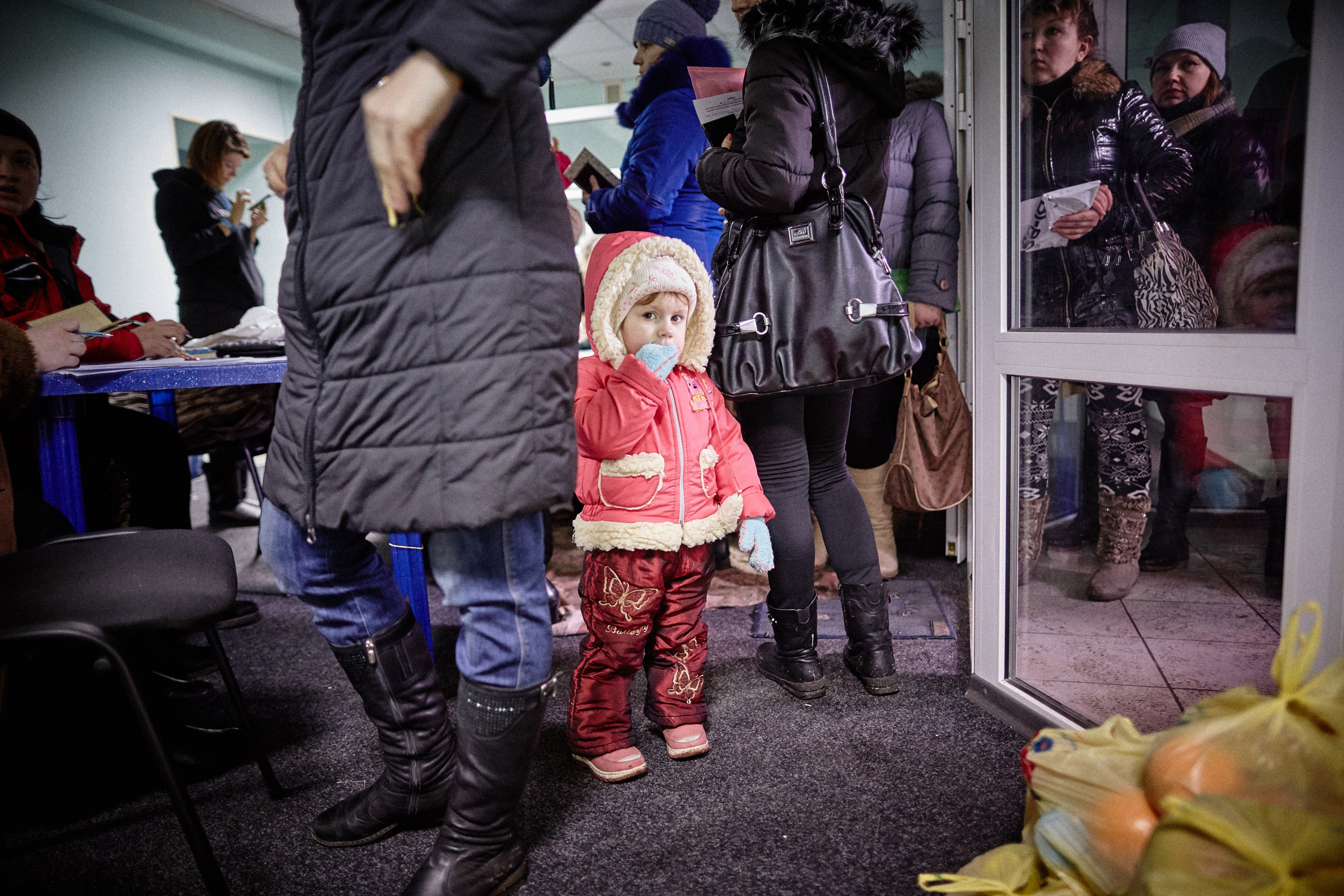 The everyday life of displaced children in Ukraine: instead of attending kindergarten and playing with other children, they stand with their mothers in line for humanitarian aid. Kramatorsk, 4 February 2015.