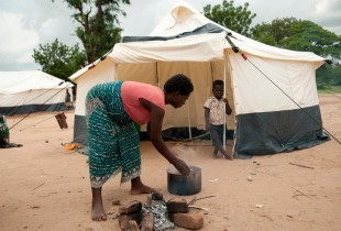 Martha Watson prepares a meal for herself and her son, who watches from their tent shelter, in a camp for people affected by the flooding, at Bangula FP School in the southern district of Nsanje.