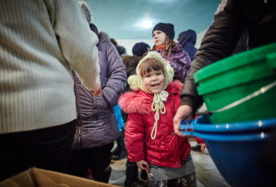 A displaced child lines up with her parents to receive UNICEF hygiene supplies at the humanitarian aid distribution centre in Svyatohirsk.