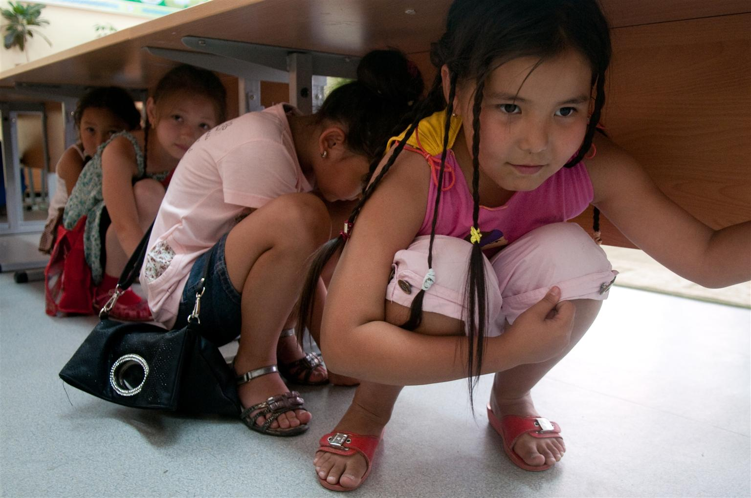 Fourth-graders seek shelter under a table during an earthquake preparedness exercise at a school in Kazakhstan.