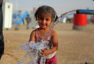 3-year-old Shahd, whose family has been displaced from the conflict-affected city of Mosul, fills a mug with water flowing from a pipe, in the Khazar transit camp in Erbil, Iraq.