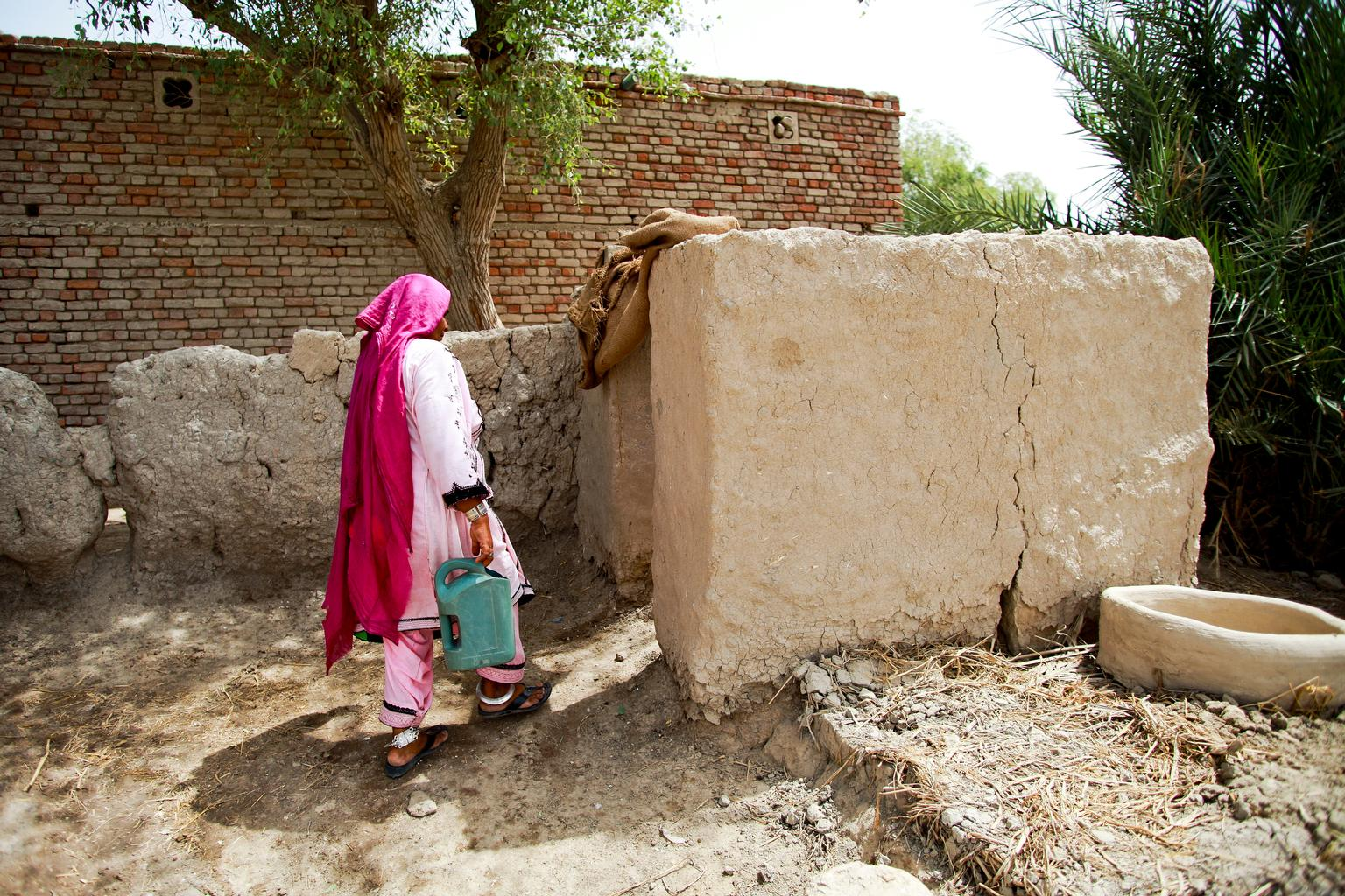 A woman in Pakistan uses pit latrine which she has constructed by herself outside her house.