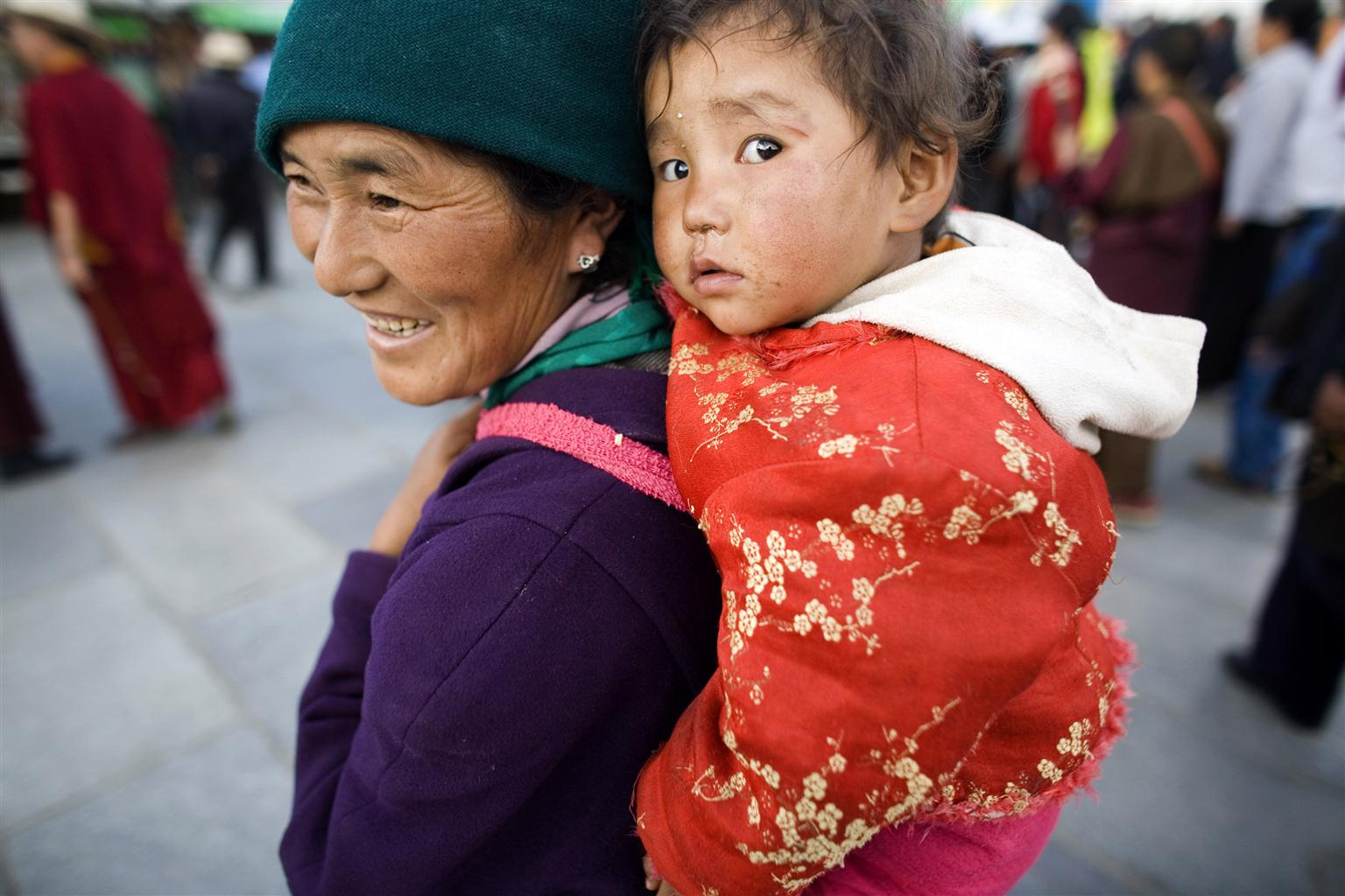 China: a mother carries her daughter.