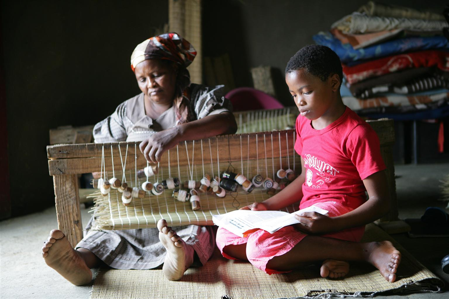 Nondumiso (9) reads a school assignment beside her grandmother, in their home in KwaZulu-Natal Province, South Africa.