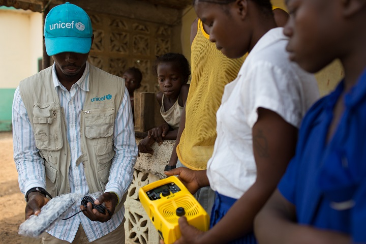 UNICEF staff member Derick Thullah explains how to use the solar powered radios as he hands them over to children in one of the hardest hit villages in Sierra Leone.