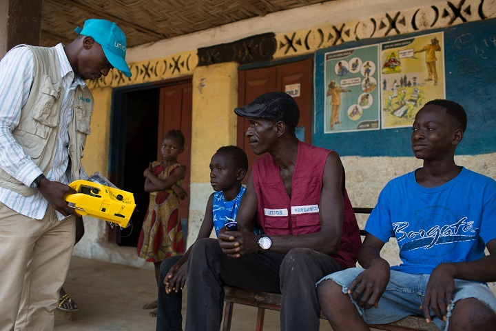 UNICEF staff member Derick Thullah explains how to use the solar powered radios as he hands them over to Ebola orphans at Pate Bana Marank village one of the hardest hit villages in Sierra Leone. (c)UNICEF Sierra Leone/2015/Tanya Bindra