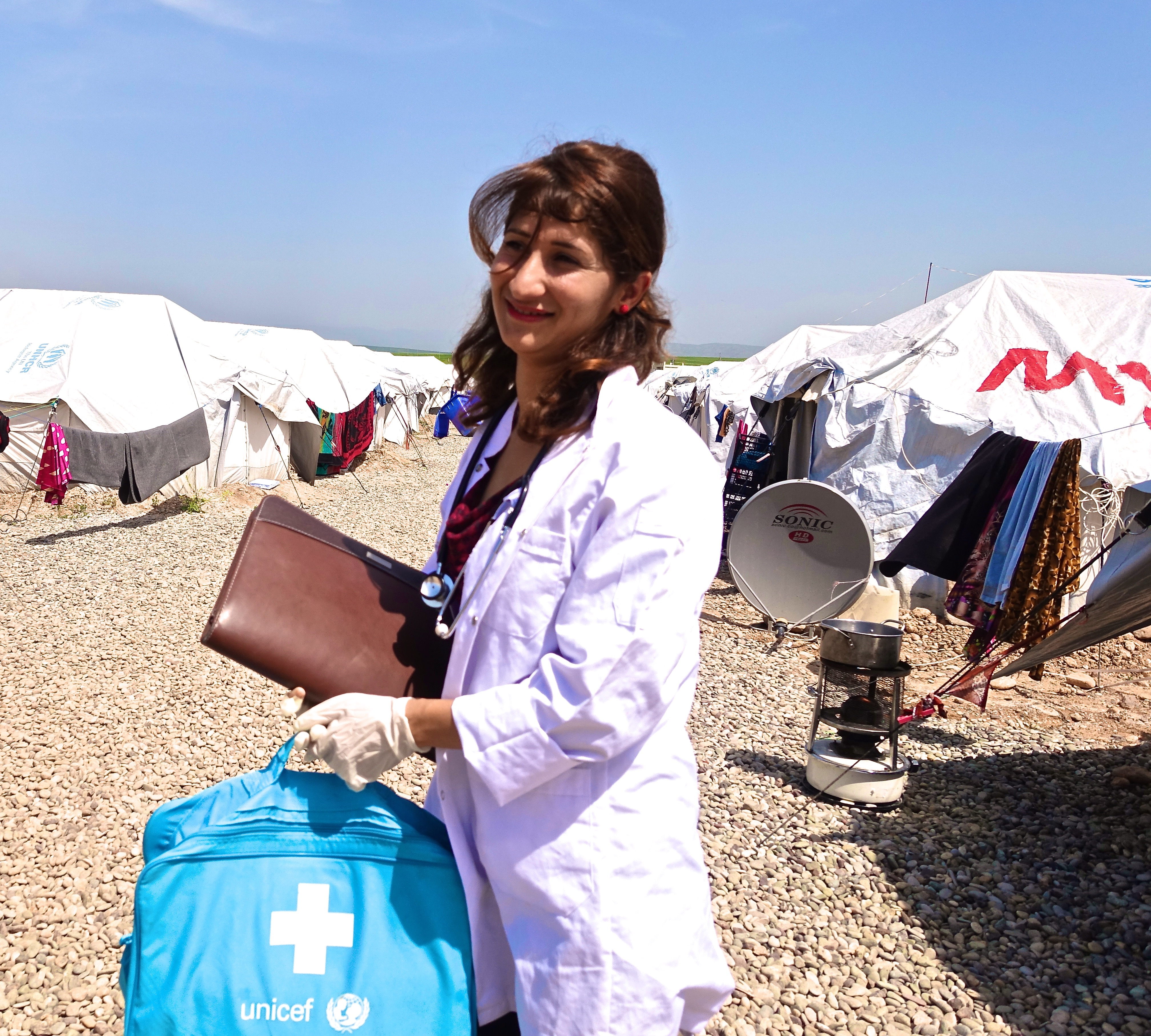 Janda stands in the camp, witht tents behind her. At the end of a long day, she is still smiling.