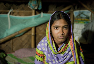 Fatema,15, sits on the bed at her home in Khulna, Bangladesh.