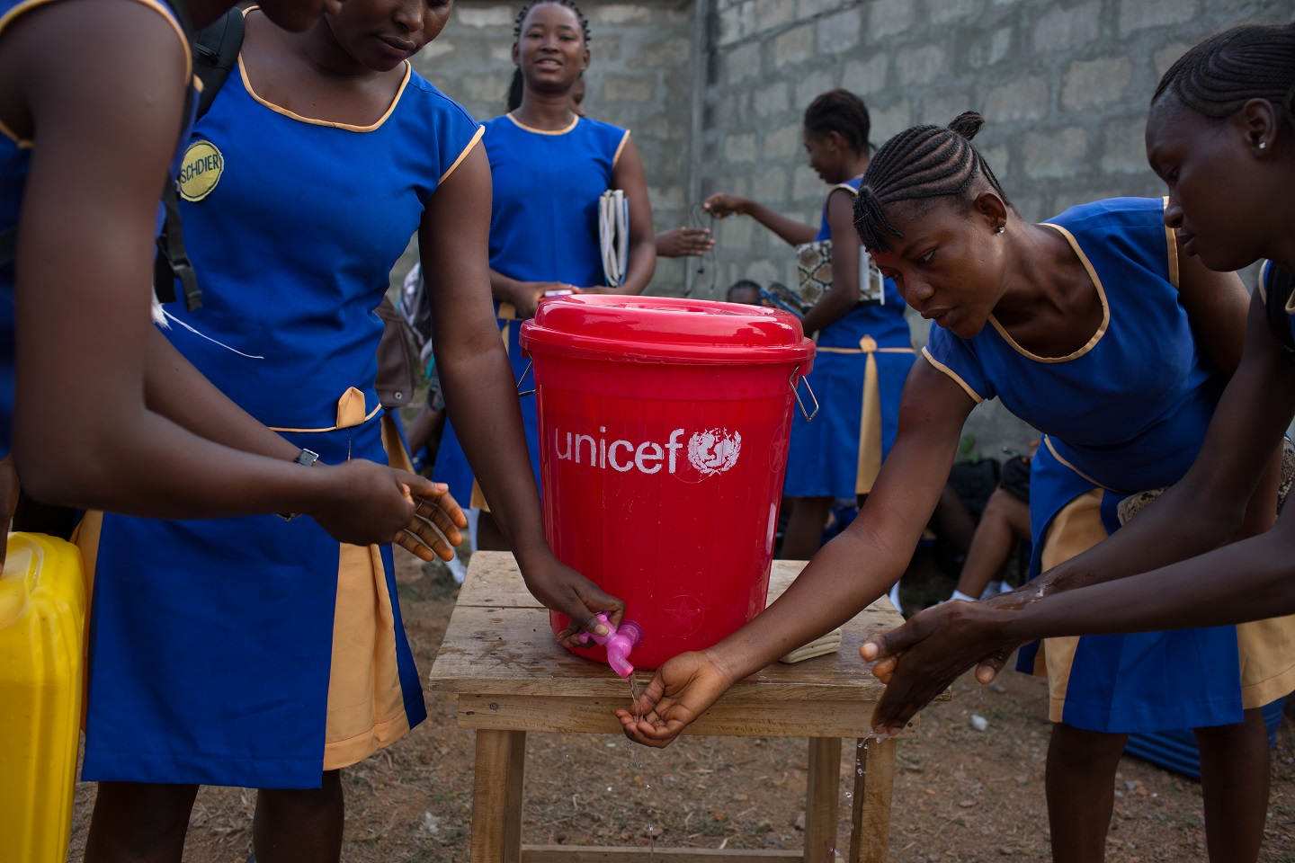 As part of Ebola protocols, all children and staff wash their hands when entering school. (c) UNICEF 2015 / Bindra