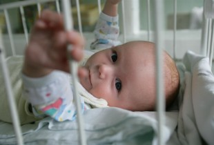 A three-month-old baby lies in a crib at a hospital in Ukraine. She was abandoned by her mother in the maternity ward.