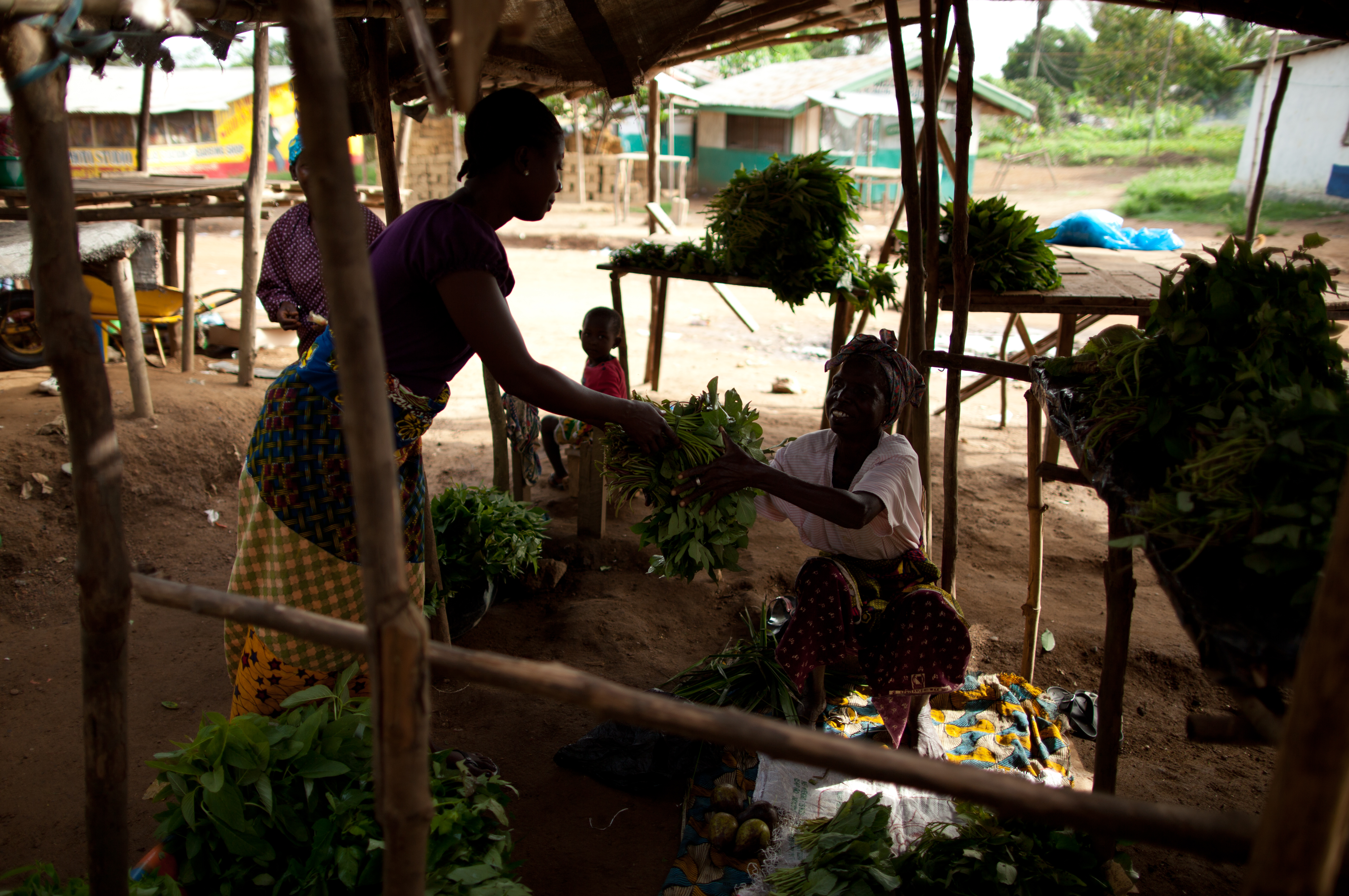 Adama Loyma buys food from the market to prepare a meal for herself and her adopted children.