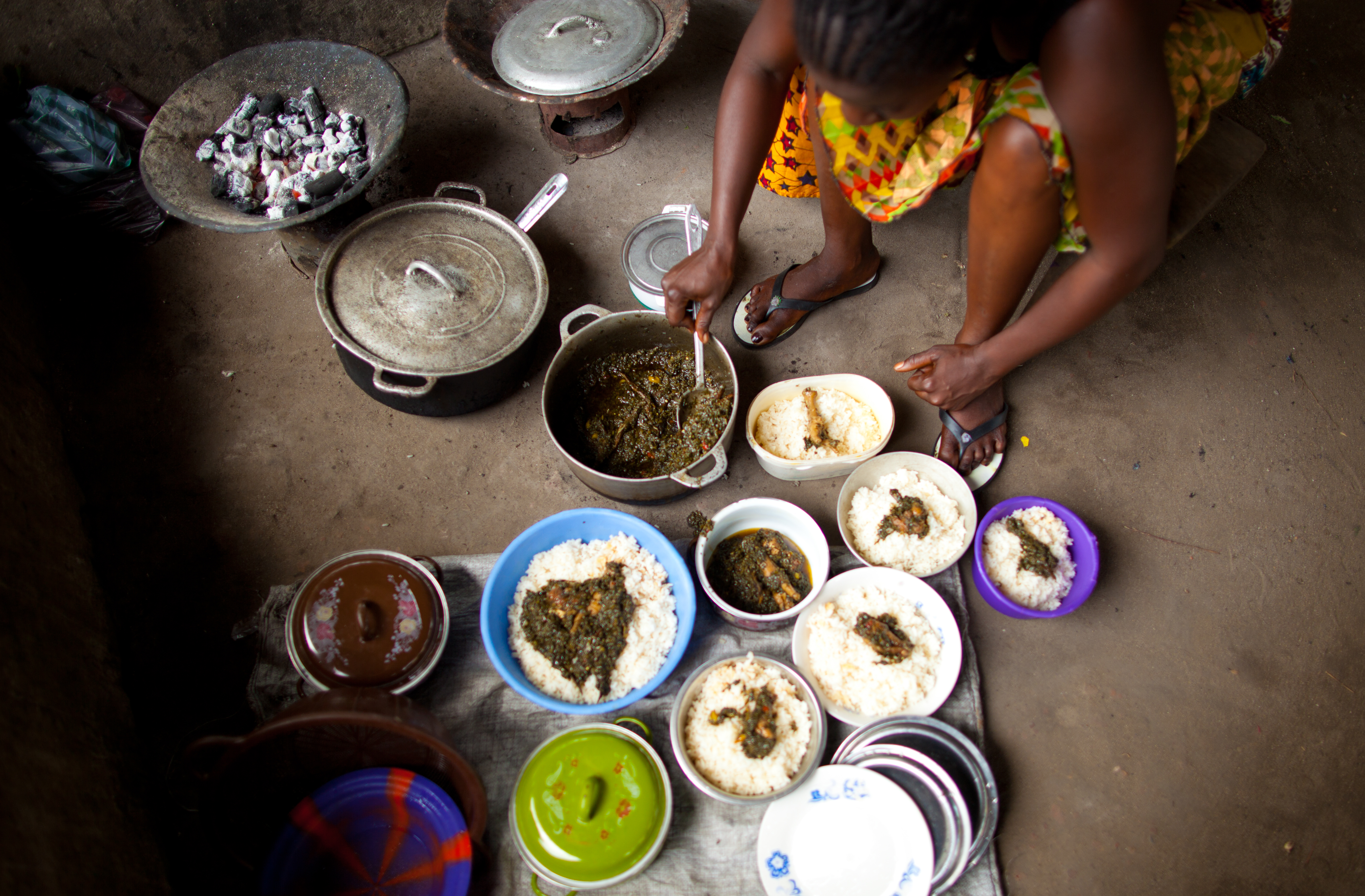 Adama Loyma dishes out meals for each of the children. Plates of food occupy the floor in front of her feet.