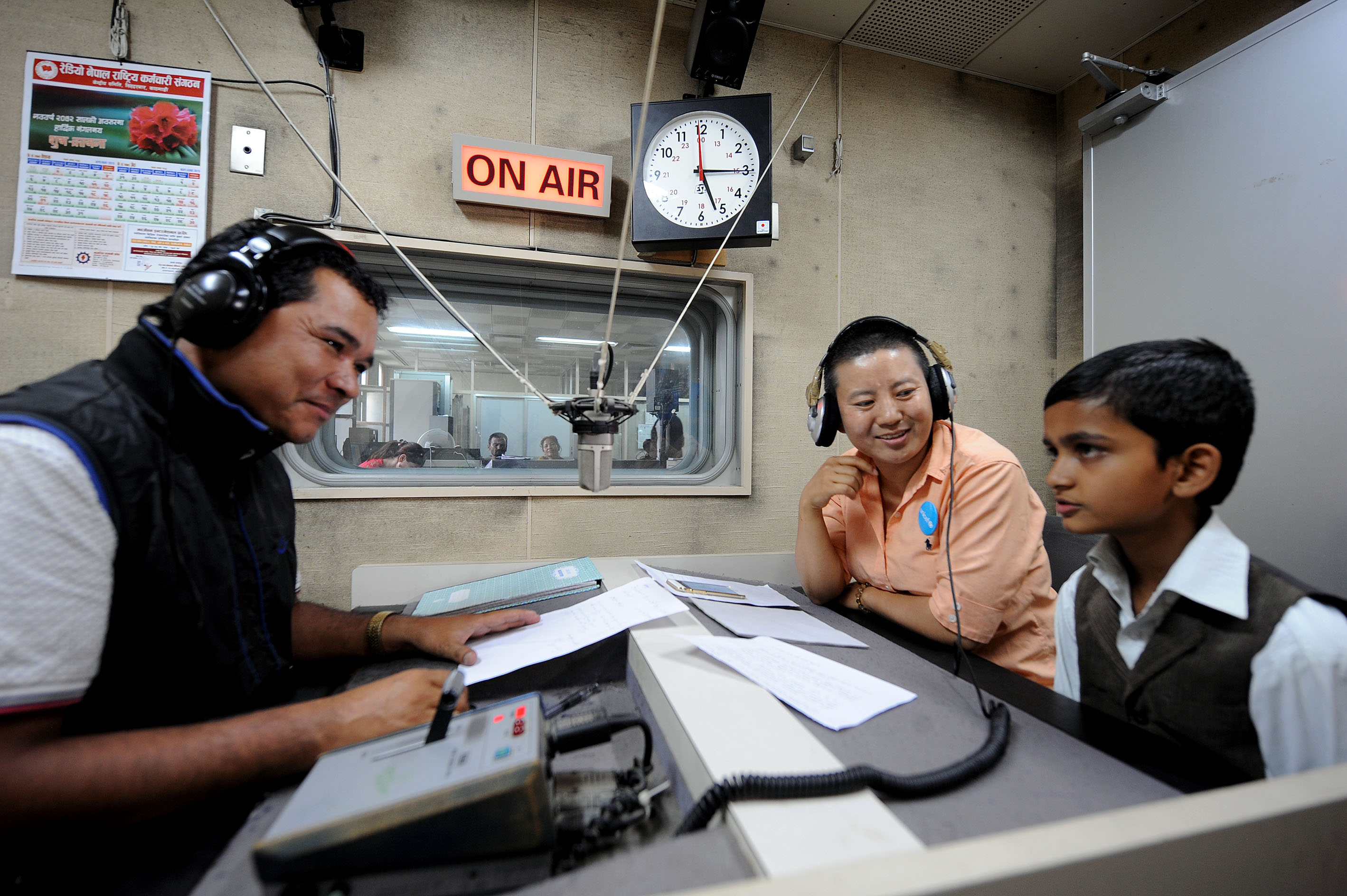 UNICEF Nepal National Ambassador Ani Choying Drolma (center) and radio anchor Ram Abiral (left) interact with child guest Subhakar Chaulagain (right) during live programming of Bhandai Sundai radio programme. Photo by Chandra Shekhar for UNICEF.