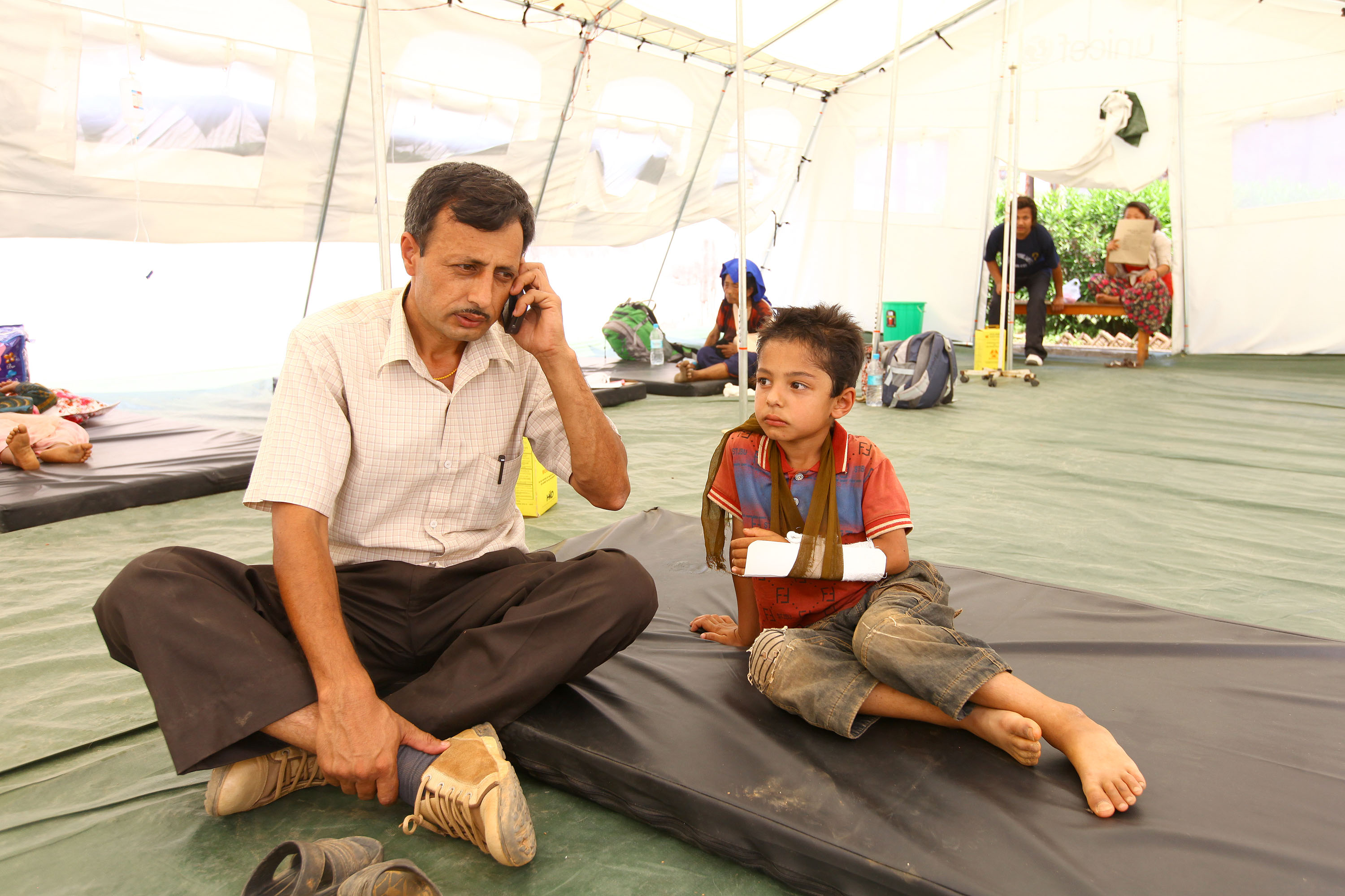 Chiranjibi Adhikari with his injured 6-year-old son, Kritagya, speaks with a psychosocial counsellor live via his mobile telephone, during a segment of the UNICEF-supported Bhandai Sundai (Saying Listening) radio programme