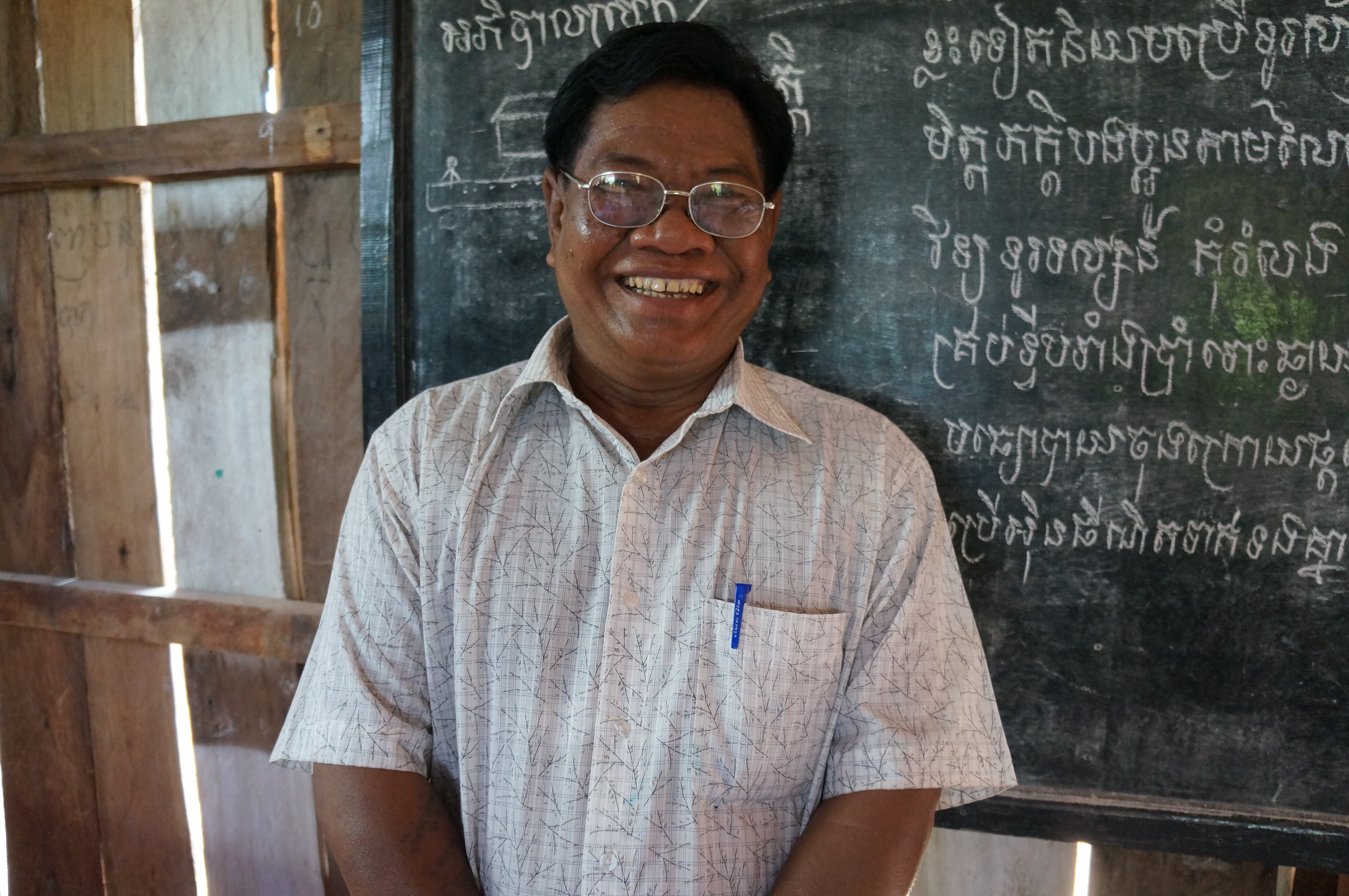 Mr. Sok Chan stands in front of the blackboard in a newly established classroom.