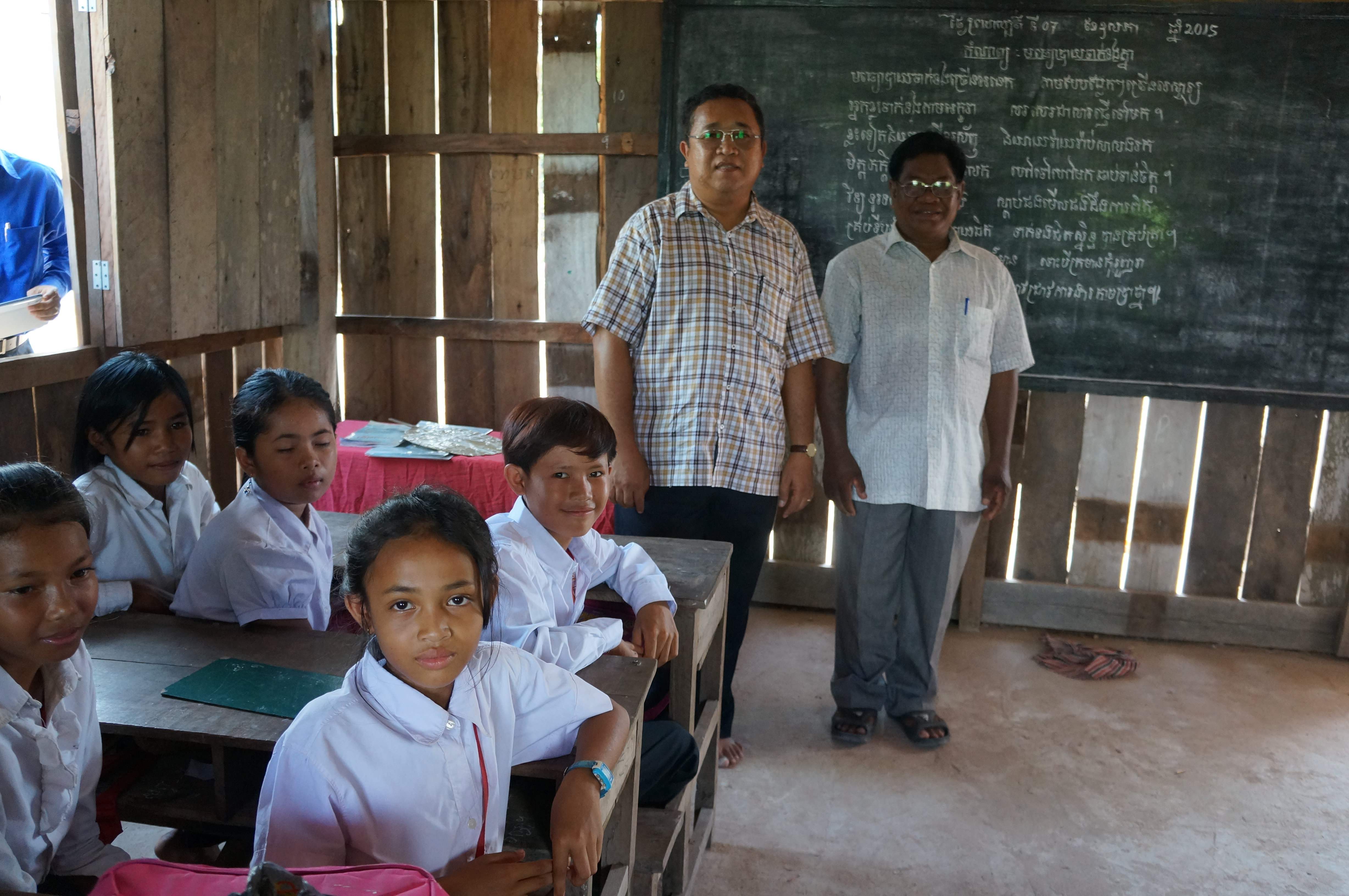 Mr. Sok Chan (right) and District Governor Chea Sambath, a strong advocate for the school, with the grade 4 students. ©UNICEF Cambodia/2015/Iman Morooka