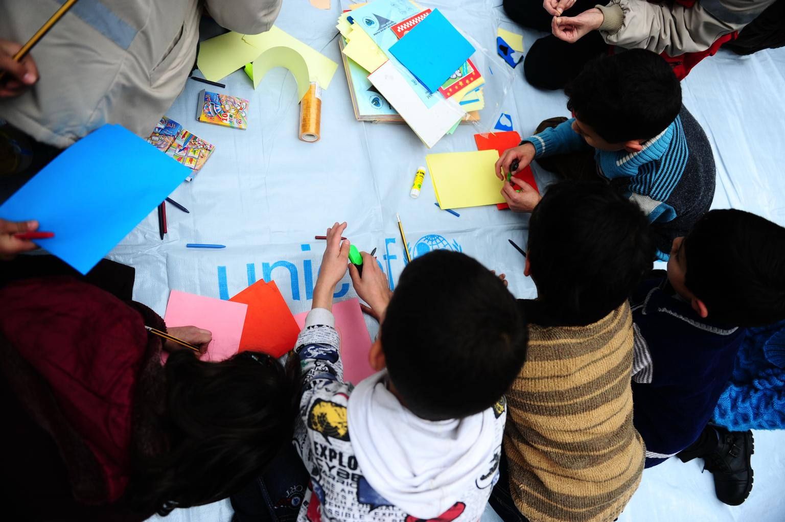 In 2014, displaced children participate in an art activity in a UNICEF-supported shelter in Homs, capital of Homs Governorate.