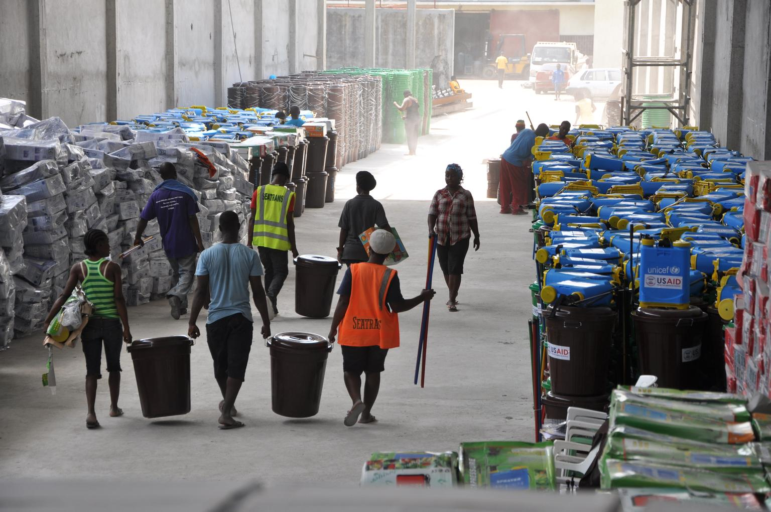 On 28 January, workers carry large buckets and other items that are part of school infection prevention and control (IPC) kits, in a warehouse in Monrovia, the capital. The logos of UNICEF and USAID (the United States Agency for International Development) – which helped fund the kits – are visible on some of the buckets and other items. The kits also contain buckets with faucets, rubber gloves and rubber boots, thermal guns, chlorine and chlorine sprayers, soap, brooms and other items for schools to implement the strict safety protocols that have been developed for the resumption of classes in the context of the Ebola outbreak. UNICEF has procured and is packaging and dispatching more than 7,000 IPC kits to over 4,000 schools in the country. Liberia, with Guinea and Sierra Leone, continues to experience widespread and intense EVD transmission. In late January/early February 2015 in Liberia, as schools prepare to reopen, UNICEF and partners are helping reduce as much as possible the risk of Ebola virus disease (EVD) transmission. Support includes training teachers to implement safety measures, such as daily temperature screenings, and supplying thermometers and hand-washing kits for schools. Because of EVD, public schools in Guinea, Liberia and Sierra Leone remained closed after the July–August break, depriving 5 million children of months of education. Amid continued school closures in Liberia and Sierra Leone, UNICEF is working with governments and communities to prepare for their eventual reopening. Schools are scheduled to reopen in Liberia on 16 February.