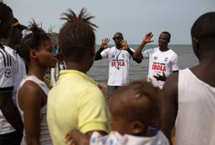 On 27 March, social mobilizers speak with residents, including children, in Freetown, Sierra Leone. a