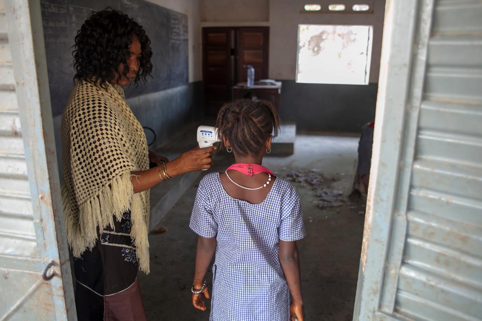 On 11 March 2015 in Guinea, a teacher uses a UNICEF-provided infrared thermometer to take the temperature of a girl as she enters her classroom, at the Mangalla school, in the town of Guéckédou, Guéckédou Prefecture. Because of the Ebola virus disease (EVD) outbreak, schools across the country remained closed after the conclusion of the July-August 2014 holidays and finally reopened on 19 January 2015.  UNICEF and partners have worked to help reduce, as much as possible, the risk of EVD transmission. Efforts have included training teachers to implement safety measures, such as daily temperature screenings, and supplying thermometers and handwashing kits for schools.