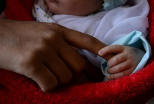 An woman holds her two-days-old son's hand while being hospitalized after having the baby.