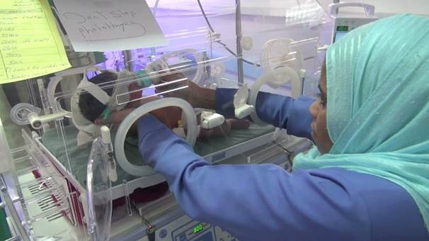 A health worker tends to a newborn baby. The health care facilities that remain open have few medicines to treat children, and essential medical supplies such as bandages, syringes and other crucial equipment are running low.