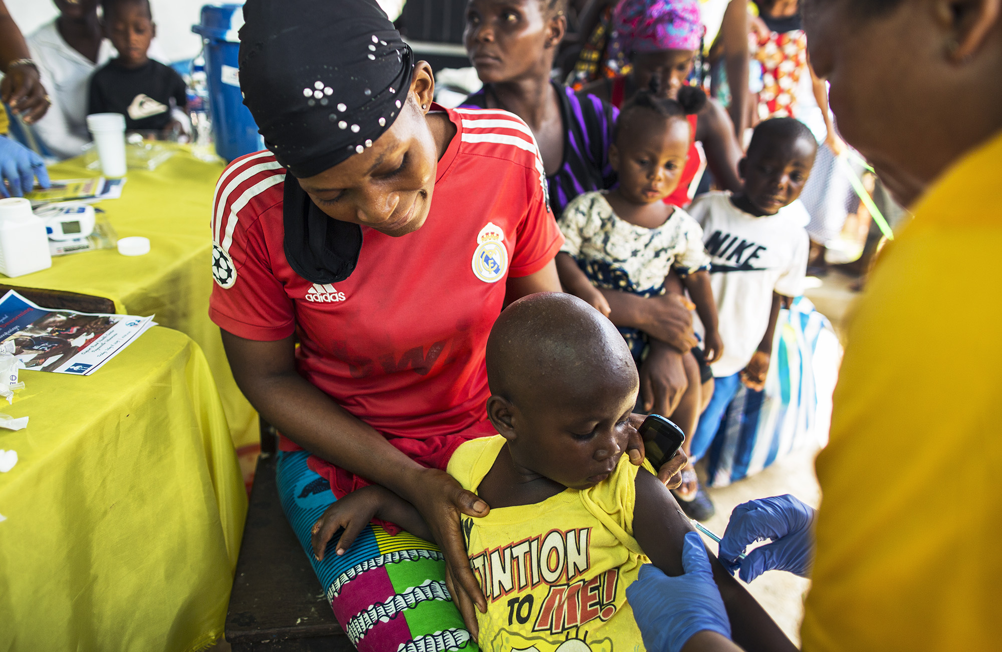 Supported by his mother, Alpha (3) looks on bravely as he receives the measles vaccination.