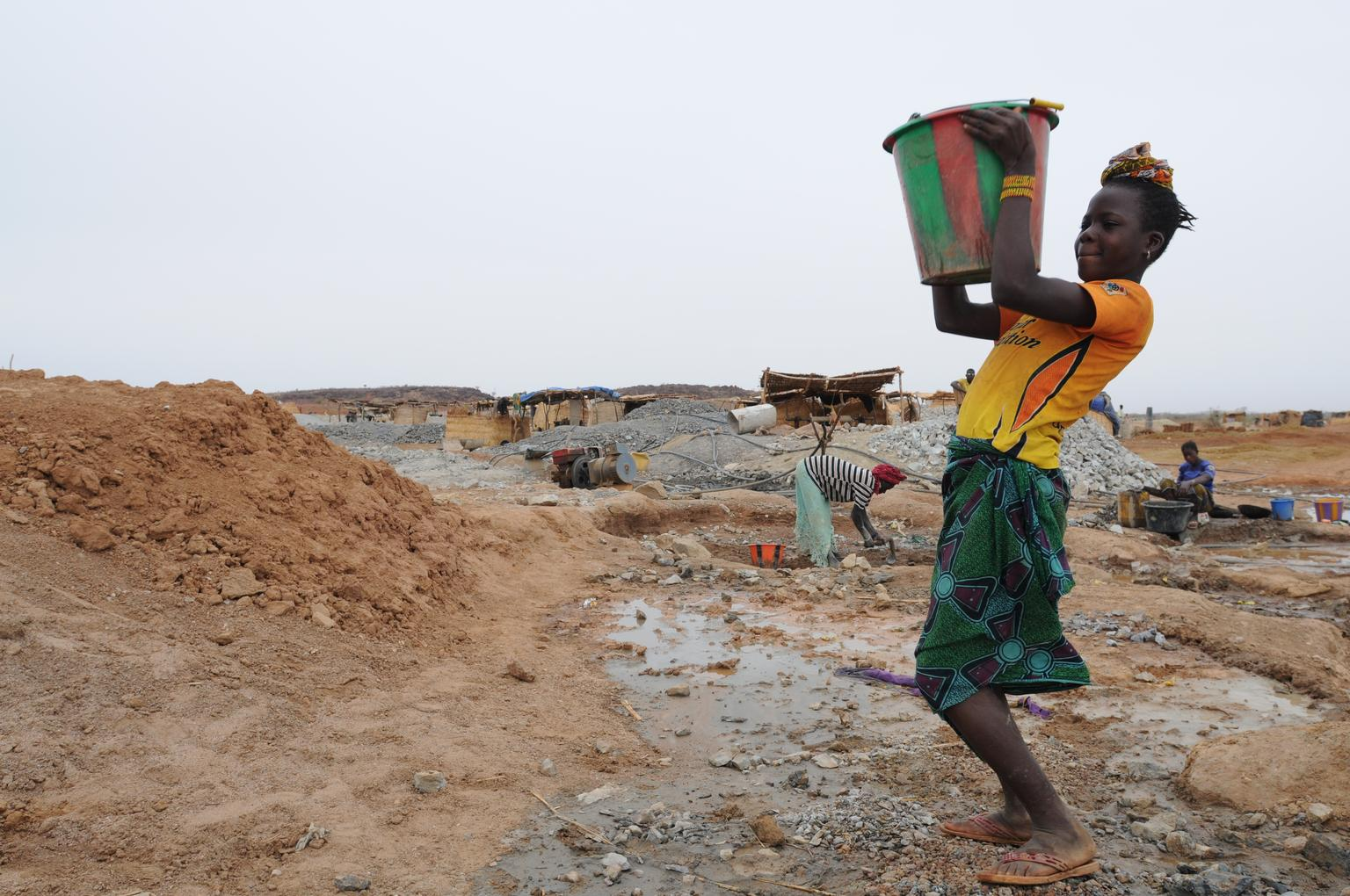 A girl carries a bucket filled with water, which she will use to wash the dust from ground rocks while panning for gold, at the Gorol Kadje mine in Burkina Faso.