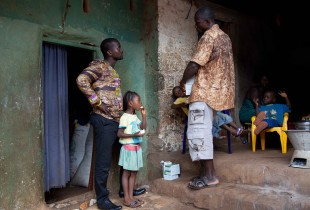 Yusuf Koroma, a social worker, chats with 4-year-old Musu Conteh's grandfather, who has been caring for her ever since her parents died of Ebola