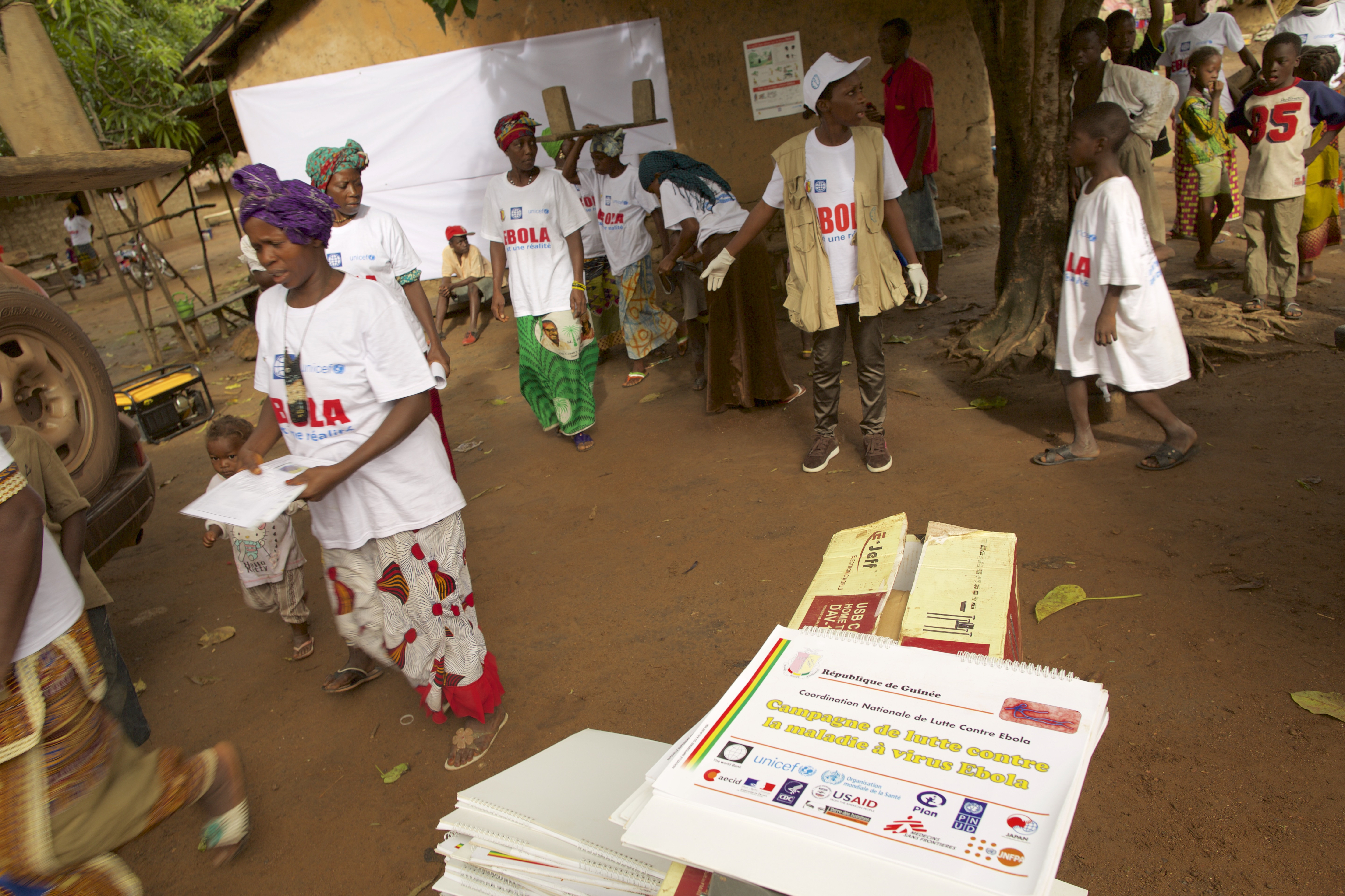 Members of UNICEF's social mobilization team in Sikhourou village use illustrated booklets to educate residents about the symptoms of Ebola and how to avoid becoming infected. ©UNICEF Guinea/2015/Tim Irwin