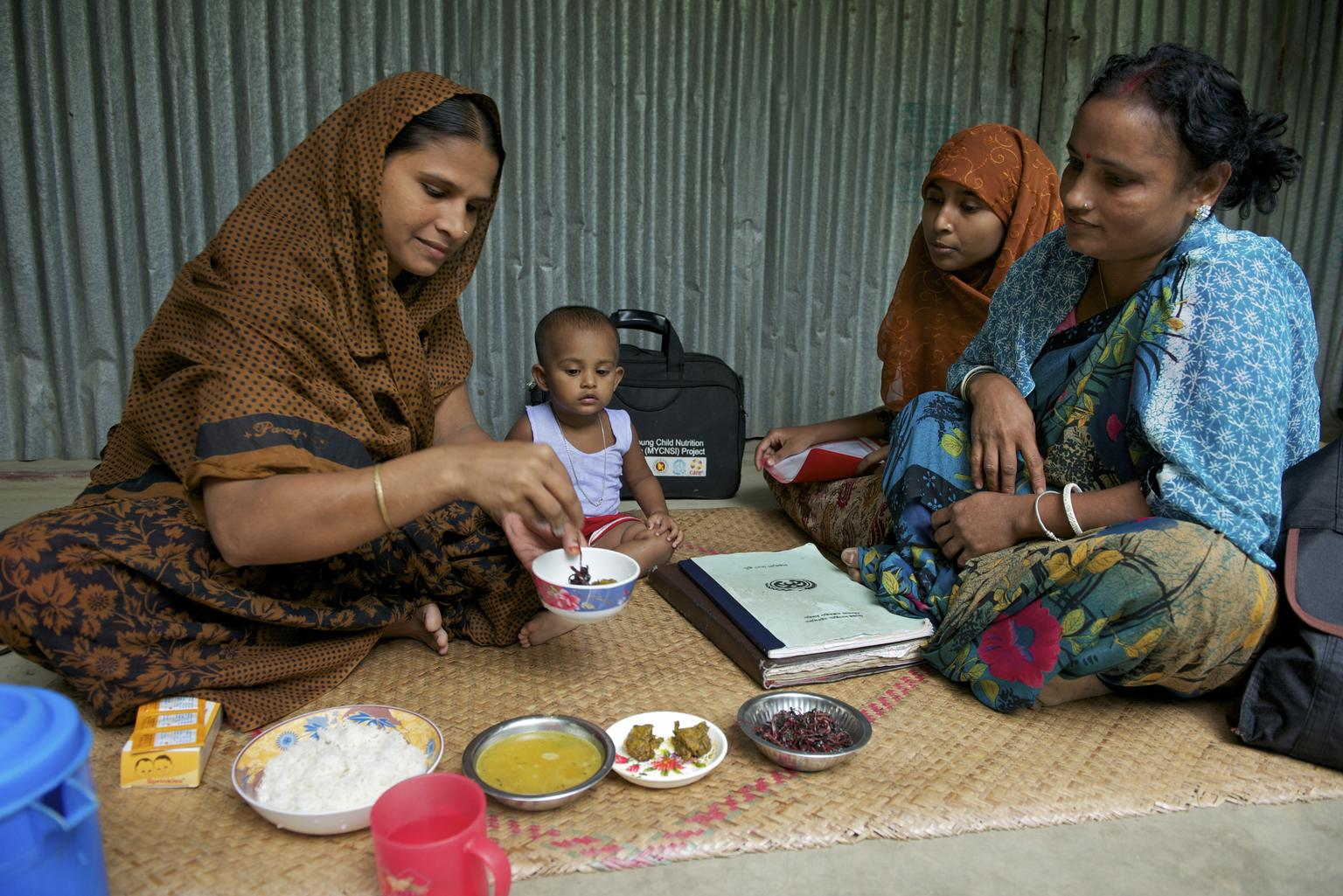 In Bangladesh, Chaya Rani (left) adds Sprinkles, a micronutrient powder (MNP), to food for her 15-month-old daughter.