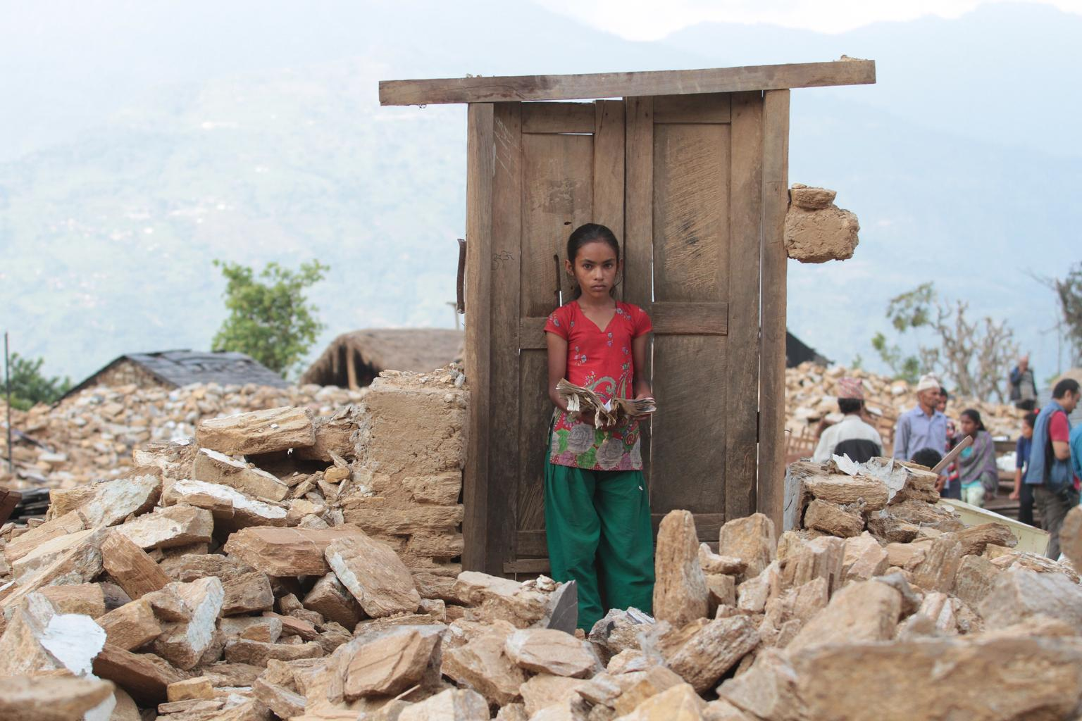 Pabitrya (13) holds a book that she found among the rubble of a destroyed school in one of the severely earthquake-affected districts in Nepal.