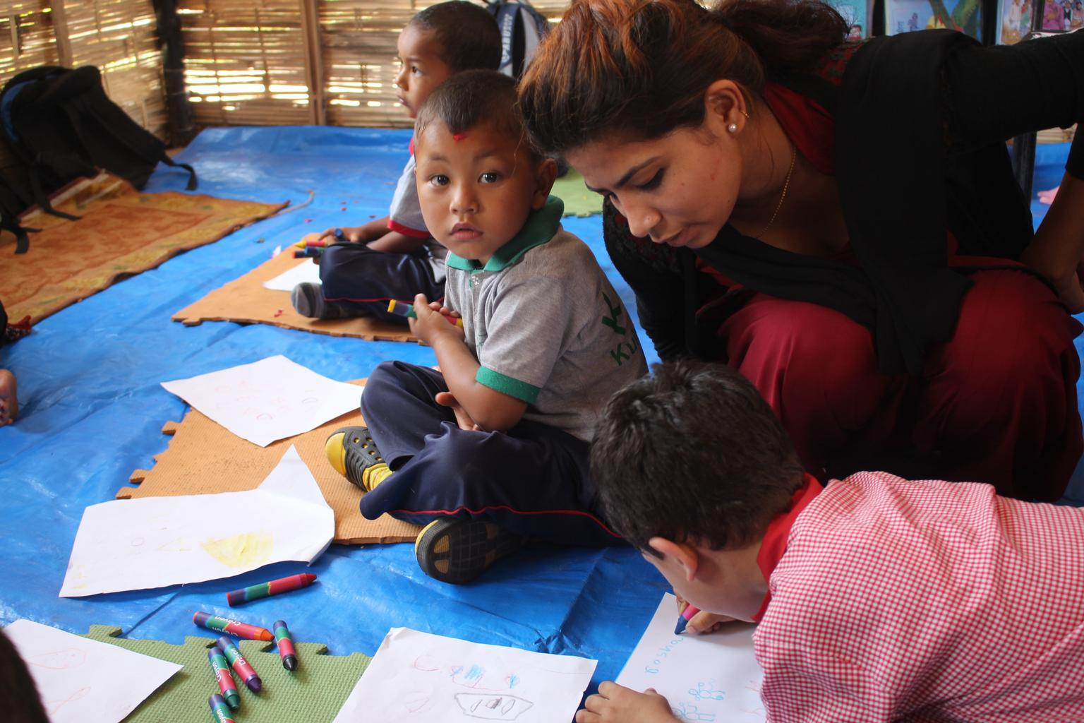 A facilitator helps one of several young boys who are drawing and colouring during an early childhood development activity in a UNICEF-supported temporary learning centre.