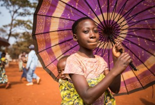 A Burundian girl carries her younger sister.
