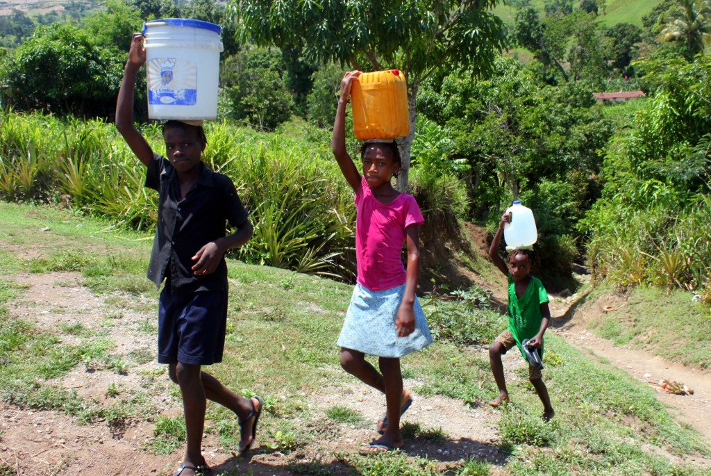 A group of children walk to collect water.