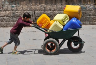 A boy pushes a wheelbarrow filled with jerrycans in Sana'a, the capital of Yemen.