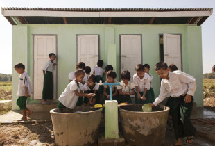 Children in Myanmar wash their hands with soap at a hand-washing station.
